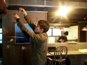 小鮎せんべいモビールを吊るすタケムラさん